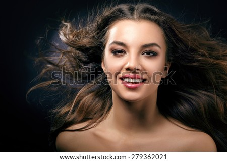 A smiling woman with flowing hair close-up - stock photo
