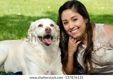 A smiling woman with her pet dog in the park. - stock photo