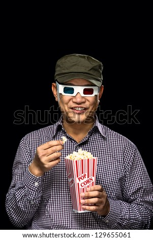 A smiling young Asian man eating pop corn on movie night - stock photo