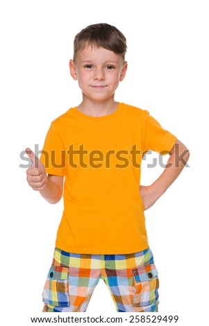 A smiling young boy with his thumb up stands against the white background - stock photo
