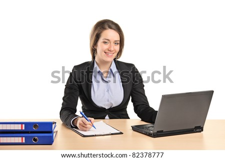 A smiling young businesswoman working on a laptop isolated on white background - stock photo