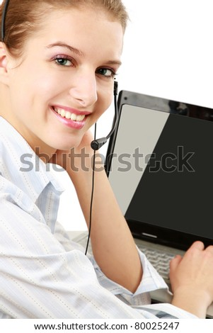 A smiling young customer service girl with a headset at her workplace, closeup, isolated on white