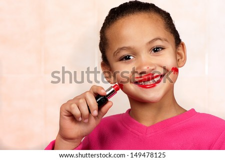 A smiling young girl applies lipstick in an unconventional manner. - stock photo