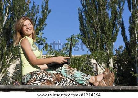 A smiling young girl with laptop outdoors - stock photo