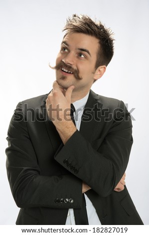 A smiling young man in business attire looks up with an idea - stock photo