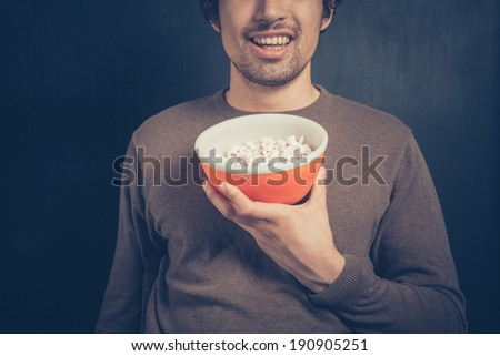 A smiling young man is holding a bowl of popcorn