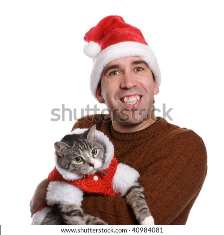 A smiling young man wearing a santa hat and holding his cat, isolated against a white background - stock photo