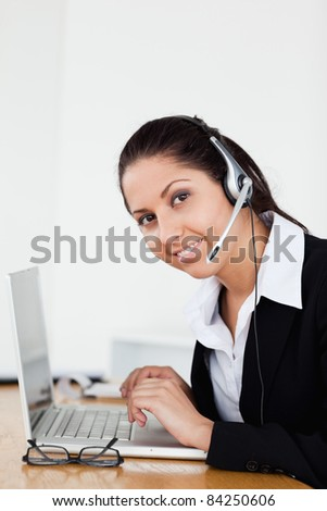 A smiling young operator with a headset is helping someone via headset in her office