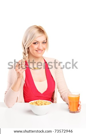 A smiling young woman at breakfast isolated on white background