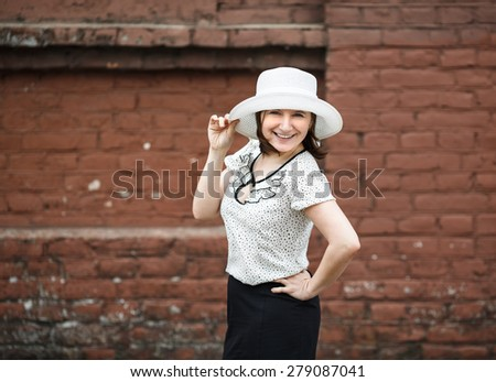 A smiling young woman in a white blouse and a hat posing against the backdrop of an old vintage brown brick wall. Female hand holds a hat.  Photo in retro style. Selective focus on model. - stock photo