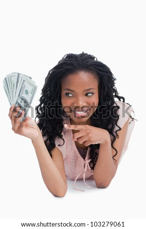 A smiling young woman is pointing at American dollars in her hand against a white background