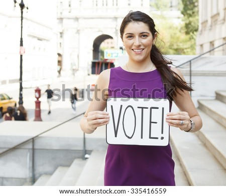 A smiling young woman on building steps wit a 'VOTE' sign. - stock photo