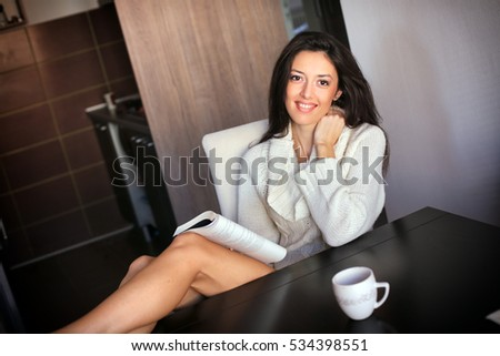a smiling young woman reading a book in her kitchen