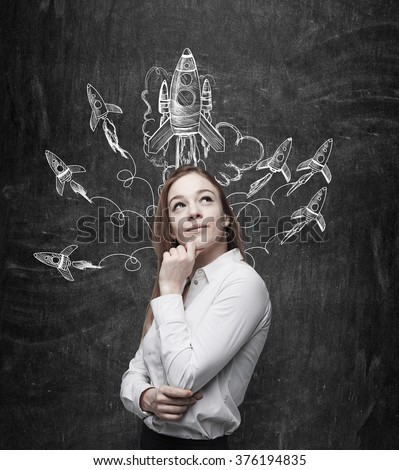 A smiling young woman standing at a black wall and looking up and aside, painted rockets flying from over her head. Concept of launching a new project. - stock photo