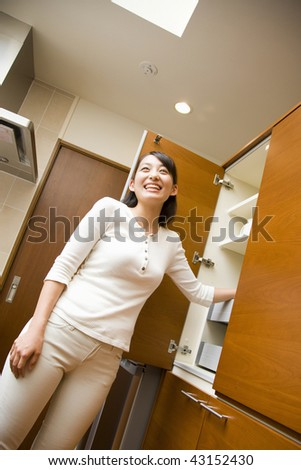 A smiling young woman standing by the cupboard