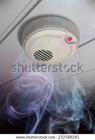 A smoke detector installed at a ceiling with smoke. Small depth of field.