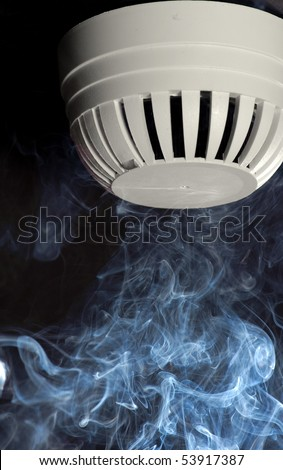 A smoke detector with rising smoke. - stock photo