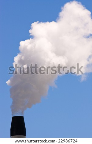 A smoking chimney against a clear blue sky - stock photo