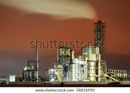 a smoking industrial power plant at night - stock photo