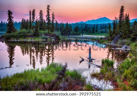 A smoky haze hangs over the distant mountains as the sun sets over a lake in Wrangell-St Elias National Park, Alaska - stock photo
