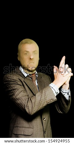 A snarling businessman with a stocking mask pulled over his head makes a handgun hesture with his index fingers and thumbs conceptual of committing armed robbery - stock photo