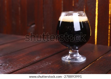 A snifter glass full of dark stout ale standing on a wooden table