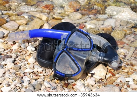 A snorkel and mask laying on top of rubber swim shoes on the beach at Spilia Bay in Meganissi island, Greece.