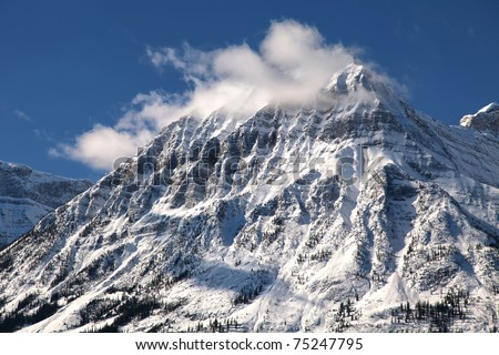 A snow capped mountain in winter, part of the Rocky Mountain range, in Jasper National Park, Alberta, Canada.