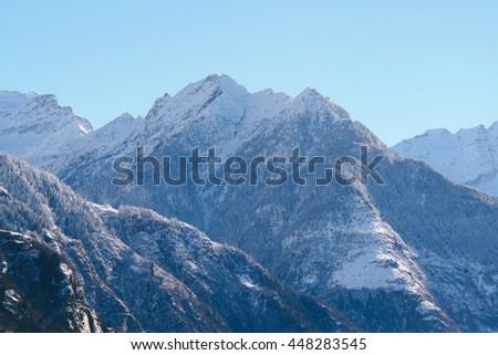 A snow-capped mountain peak of the Alps in southern Switzerland. Photo taken in Blenio valley, canton Ticino (Switzerland).