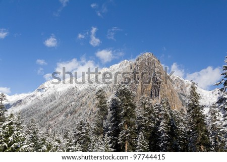 A snow-capped mountain peak under a blue sky with clouds. - stock photo