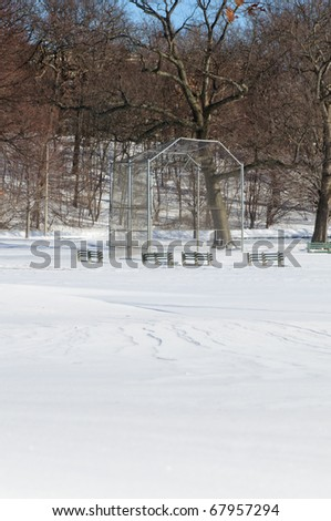 A snow-covered baseball field in winter in vertical