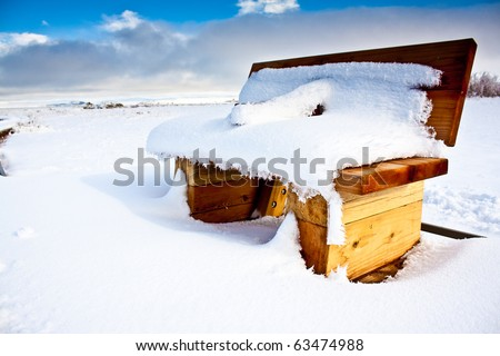 A snow covered bench in a snowy large field with a blue sky and some clouds - stock photo