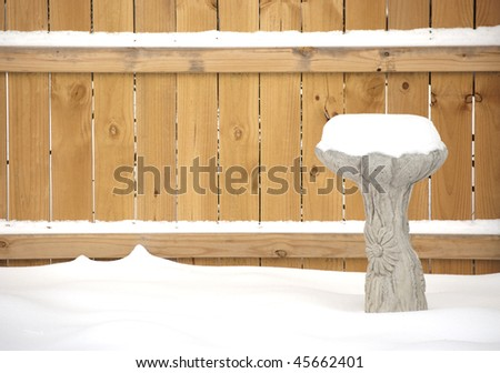 A snow covered birdbath, made of sculptured cement, in front of a wooden fence. Focus is on the birdbath.