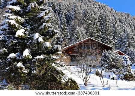 A snow covered chalet in an alpine setting at a ski resort in the mountains. - stock photo