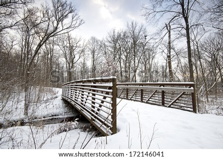A snow-covered footbridge spans a small creek at Warrenville Grove Forest Preserve in DuPage County, Illinois. - stock photo