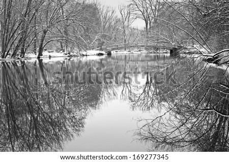 A snow covered footbridge spans the DuPage River in winter at Pioneer Park in Naperville, Illinois. - stock photo