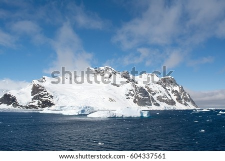 A snow covered island sits alone and peaceful at the pole.
