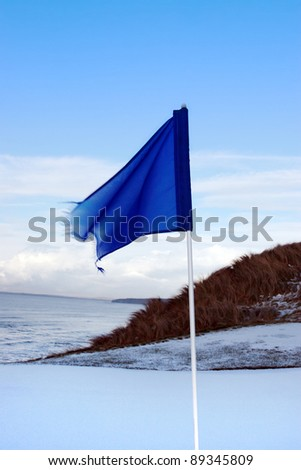 a snow covered links golf hole in ireland in winter weather with blue flag - stock photo