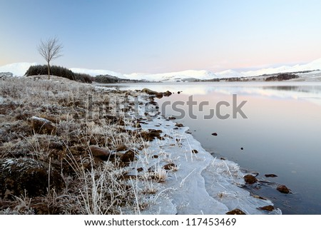 A snow covered Rannoch moor and Loch Tulla, with the snow covered Black mount in the distance. - stock photo