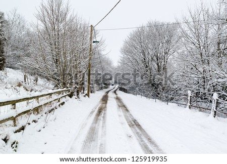 A snow covered road in winter - stock photo