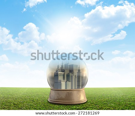 A snow globe with a city surrounded by pollution and smog on a perfect flat green lawn against a blue sky with white clouds - stock photo