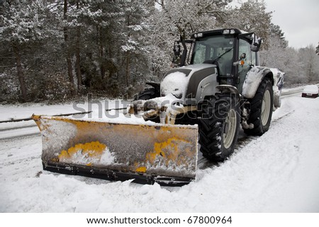 A snow plough tractor with a yellow scoop on a snowy road in England. - stock photo