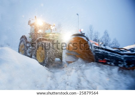 A snow plow clearing a road in winter - stock photo