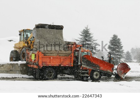 A snow plow truck getting topped off with salt before heading out to plow the  roads. - stock photo