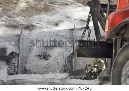 A snow plow truck on a Quebec rural road pushing the snow on the side - stock photo