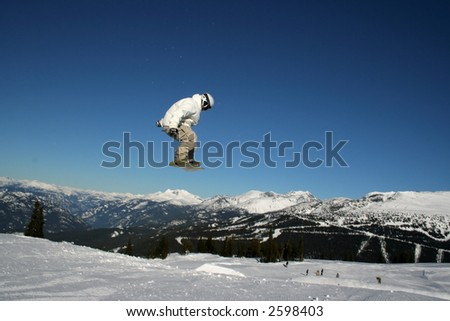 A snowboarder about to land after a short flight.
