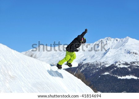 a snowboarder comes in to land on a bank of snow with arm raised in victory