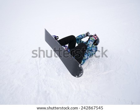 A snowboarder demonstrates snowboard actions. - stock photo