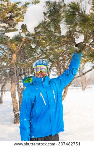 A snowboarder enjoying life, playing with snow, resting at a ski resort. Active man in ski goggles, standing in the sun rays and smiling while looking at camera. - stock photo