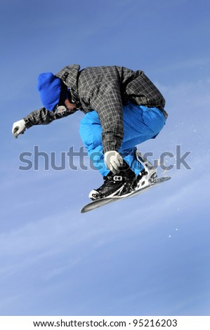 a snowboarder performing a jump against a blue sky in blue clothing